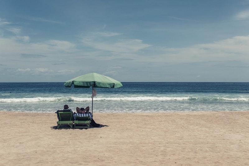 Två personer njuter av solen och havet i en varsin solstol.